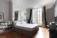 ensuite master bedroom with a queen-sized bed, TV, sitting area, some selection of books, elaborate