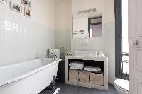 sophisticated bathroom with bathtub, sink, and toilet in a 4-bedroom Paris luxury apartment