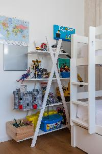 sweet bunk bedroom with shelves filled with toys in Paris luxury apartment
