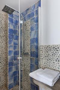 faded blue-tiled and cobbled-stone walled shower area with rainshower in Paris luxury apartment