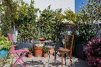sky-high terrace with chairs surrounded by thriving plants in Paris luxury apartment