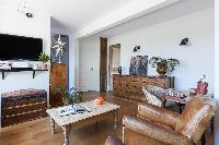 a charming living room with antique wooden chest and cabinets, and softened leather armchairs in Par