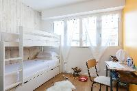 sweet bunk bedroom with yellow wall on one side and blonde wood wall on the other in Paris luxury ap