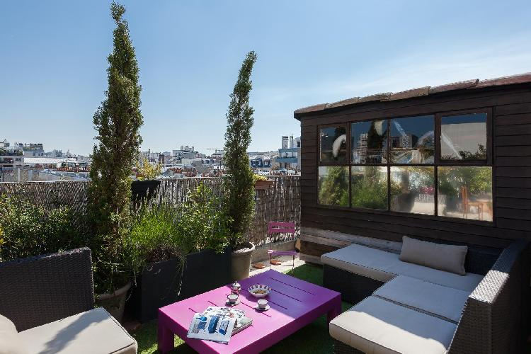 wide windows open onto home's sky-high terrace with a wicker sofa, surrounded by thriving plants, an