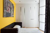 second sitting room  in vivid yellow  with black sofabed beneath framed artwork in Paris luxury apar