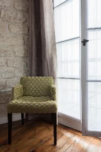 pickled-colored chair beside gray draped windows in Paris luxury apartment
