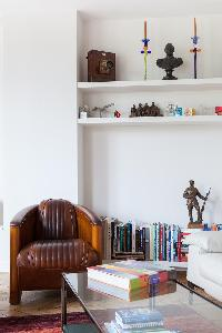honeyed wood armchair, bookshelves, glass coffee table, and some artifacts in Paris luxury apartment