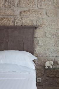 cozy master bedroom with a queen-size bed and exposed stone wall in Paris luxury apartment