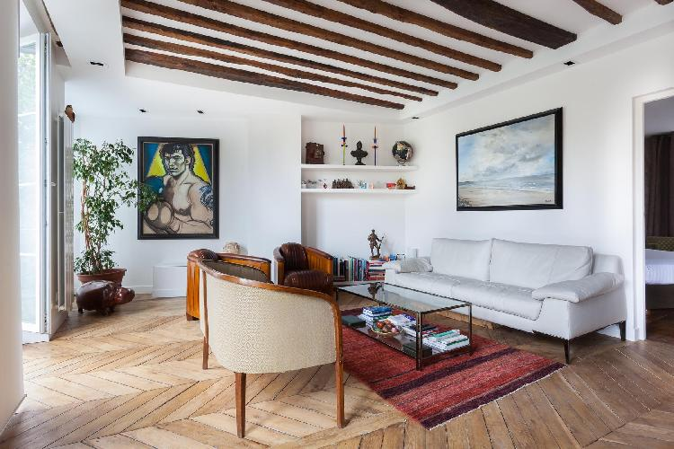 open-plan living area with softly-colored sofa, exposed stone wall, beamed ceiling, and original art