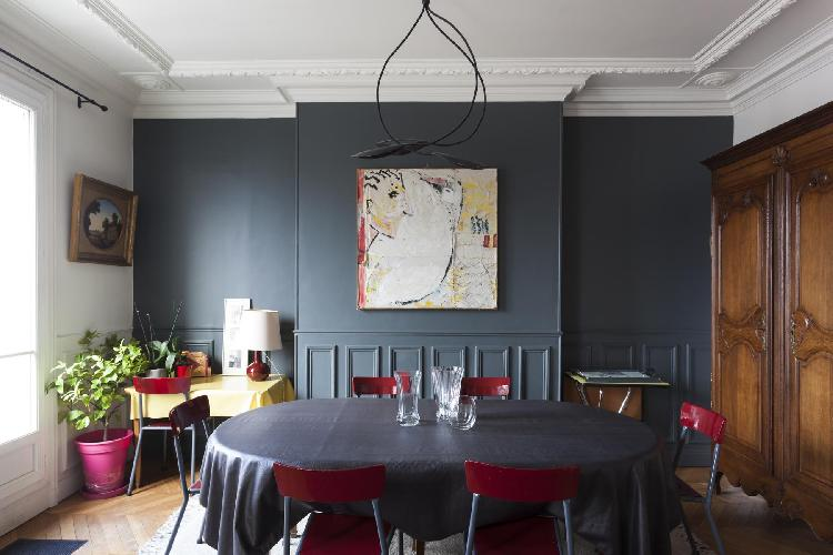 dining table set with red chairs beneath a modern artwork in Paris luxury apartment