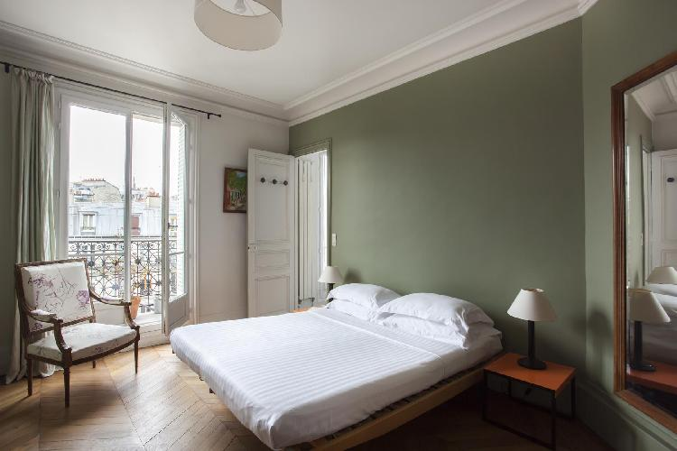 green master bedroom with a queen-size bed, Juliet balcony and an ensuite bathroom in Paris luxury a
