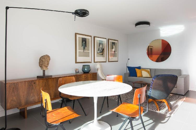 living and dining area with gray sofabed, a pair of modish armchairs, and white round dining table f