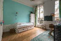 turquoise-walled bedroom with trundle bed in Paris luxury apartment