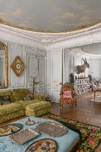 classic living room with paneled walls, ornate mirrors, and a high moulded ceiling in Paris luxury a