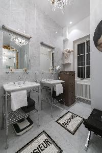marble-tiled bathroom with double sink in Paris luxury apartment