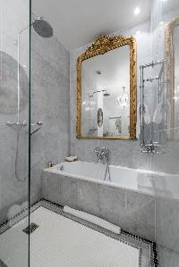 marble-tiled bathroom with integrated shower in Paris luxury apartment