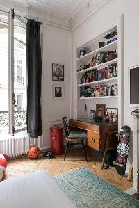 antique study beneath piles of books in Paris luxury apartment
