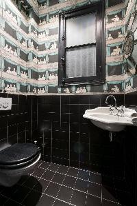 black-tiled toilet with patterned wall paper in Paris luxury apartment