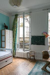 green board, trundle bed, and green-and-turquoise drape window in Paris luxury apartment