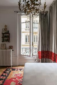 colorfully contemporary bedroom with red and gray drape in Paris luxury apartment