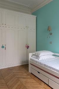 turquoise-walled bedroom with single trundle bed with lots of closets in Paris luxury apartment