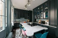 sleek kitchen in shades of grey with marble table with grill surrounded with colorful chairs in Pari