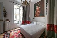 colorfully contemporary bedroom with red and gray drape, double bed beneath framed artwork in Paris