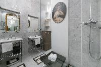 marble-tiled shower area with double sink in Paris luxury apartment