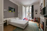 gray-and-white double bed with ornamental fireplace beneath a wide television in Paris luxury apartm