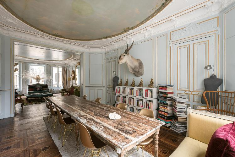classic dining room with row of Buddhas, bookshelves, a long wood dining table with 8 brass seats. a