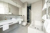 elegant en suite bathroom fitted with a bathtub, double basin, shower, and toilet in a Paris luxury