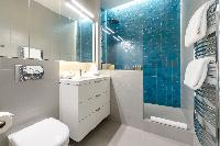 modern bathroom in its refreshing azure blue and grey hues in a Paris luxury apartment
