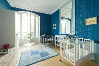 a nursery room in blue hue with a baby cots and double bed in a Paris luxury apartment