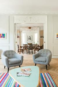 grey-colored seats with a rainbow-colored carpet lied on the parquet-floored in a Paris luxury apart