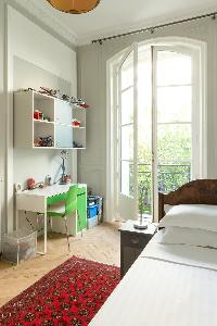 third bedroom with single bed, some interesting toys, study desk, and French window in a Paris luxur