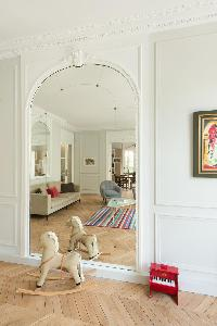 rocking pony and red toy piano facing the big mirror in a Paris luxury apartment