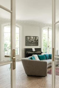 A French door opens up to a stlish living area with long grey sofa in a Paris luxury apartment