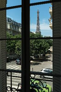 stunning Eiffel tower view from a French window in a Paris luxury apartment