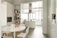 stylish well-equipped kitchen with round white table for 4 in a Paris luxury apartment
