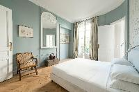 serene master bedroom in a pretty bluish grey hue with a king-size bed and an elegant ensuite in a P