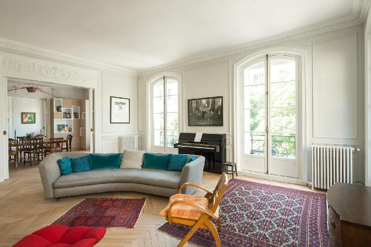 long grey sofa with colorful carpet rug and old piano overlooking the courtyard  in a Paris luxury a