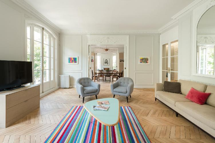 sitting room with a beige sofa and grey-colored seats with a rainbow-colored carpet lied on the parq