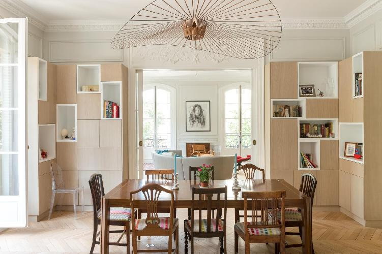 cozy dining area with wooden table for 8 and stylish shelves in a Paris luxury apartment