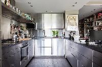 a corner kitchen with steel cabinets in a Paris luxury apartment