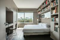 elegant master bedroom with queen size bed, bookshelves, study desk and bright window overlooking th
