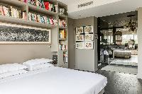 stylishly decorated master bedroom with bookshelves and ensuite in a Paris luxury apartment