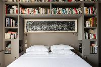 stylishly decorated master bedroom with bookshelves and in a Paris luxury apartment