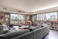 cozy living area with a collection of films and artworks, grey sofa, and spectacular view of Paris