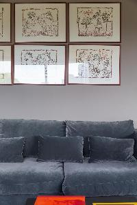 comfy elephant grey sofa with framed artworks in a Paris luxury apartment