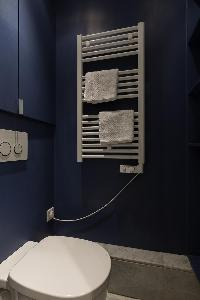 toilet in steel blue hue with towel rack in a Paris luxury apartment